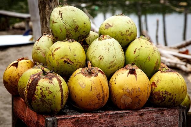 Viele frische grüne kokosnüsse, die mit einem stapel ausgekleidet sind. closeup marktstände auf bali