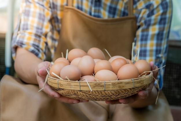 Viele frische hühnereier in einem weidenkorb, die landwirte von hühnerfarmen sammeln.