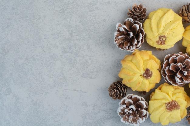 Viele frische leckere kekse mit kleinen tannenzapfen auf weißem tisch.