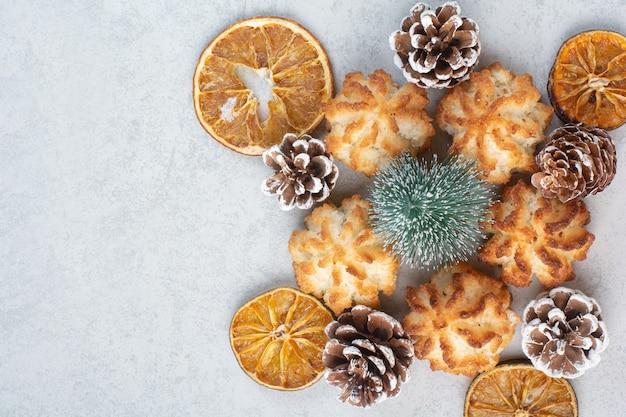 Viele frische leckere kekse mit kleinen tannenzapfen und getrockneten orangen.