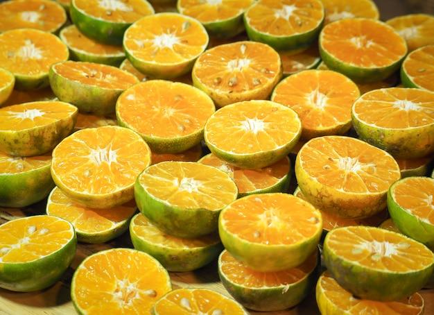 Viele frische orangen in scheiben geschnitten und ganze zitrusfrüchte, mandarinen oder süße grüne thai-orange für saft.
