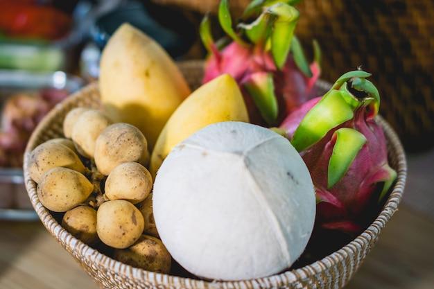 Viele früchte auf dem tisch, wie z. b. wollongong, brieten kokosnuss und drachenfrucht im korb auf dem esstisch