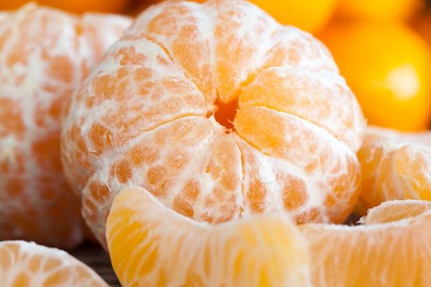 Viele ganze und durch scheiben geteilte teile reifer mandarine