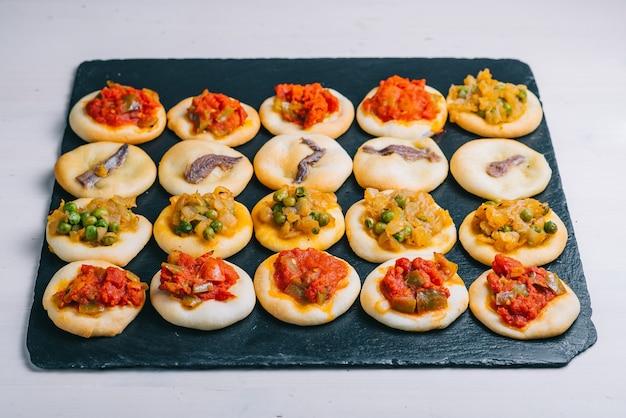 Viele gebackene mini-pizzen. traditionelles spanisches gebäck mit gemüse.