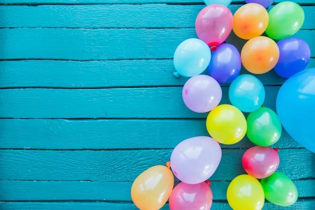 Viele geblasene ballone auf gemaltem blauem hölzernem hintergrund