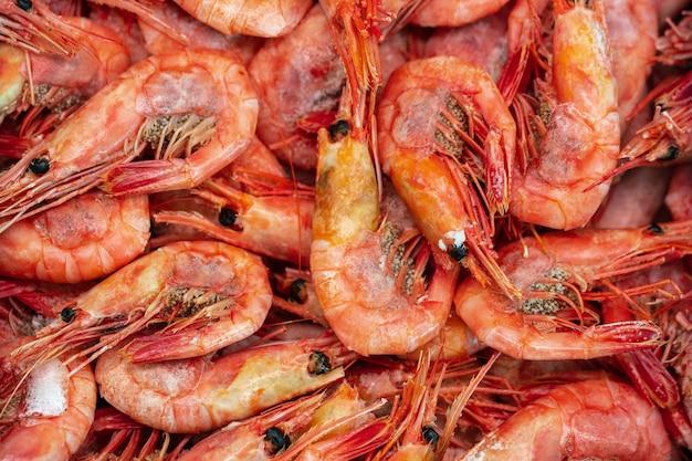 Viele gekochte gefrorene wilde garnelen mit kaviar in meerwasser gekocht. hintergrund der kleinen wasserkrebstiere der gruppe. garnelen - asiatische meeresdelikatessenküche als vorspeise. nahaufnahme flach von leckeren meeresfrüchten.