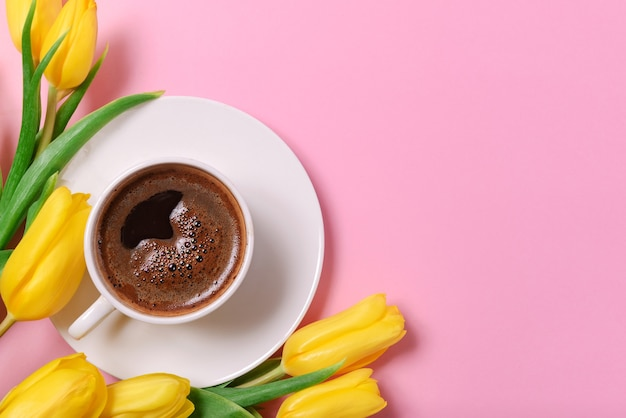 Viele gelbe tulpen, eine tasse schwarzen kaffee auf einer rosa oberfläche, ein platz für die inschrift