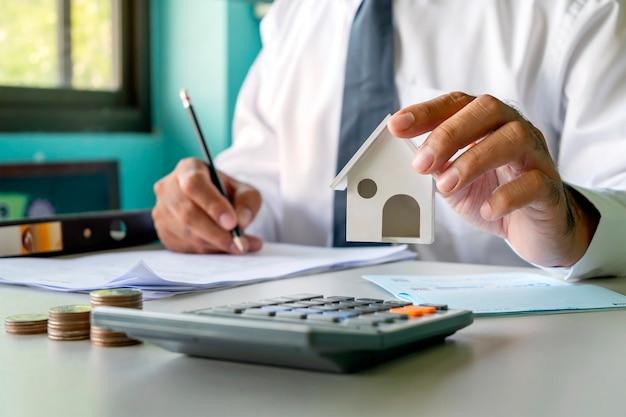 Viele geldhaufen und investoren schütteln sich die hand mit dem konzept der immobilienhypotheken