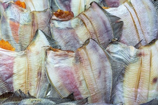 Viele gesalzene getrocknete fischozeanscholle. hintergrund von gruppenplattfischen mit kaviar. stockfisch asiatische schmankerlküche als vorspeise. nahaufnahme flacher lay-blick auf zubereitete und verzehrfertige pazifische meeresfrüchte.