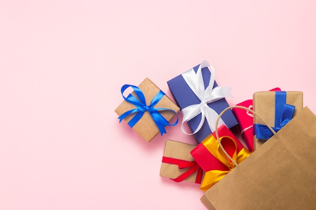 Viele geschenkboxen fallen aus der verpackung für den rosafarbenen hintergrund der einkaufspfanne. urlaubskonzept