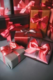 Viele geschenkboxen. geschenke in handwerk und farbigem papier mit roten schleifen verziert.