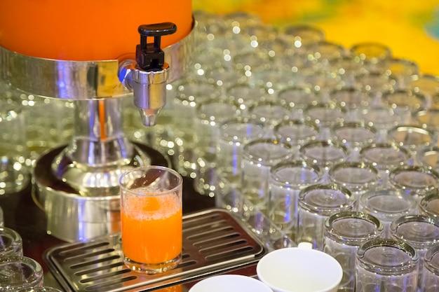 Viele gläser mit orangensaft auf buffettisch-lebensmittelhintergrund