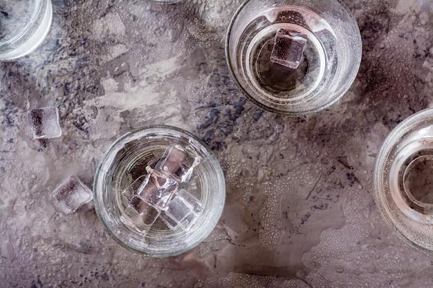 Viele gläser wasser spritzten mit tropfen und stücken eis auf einer grauen tabelle. ansicht von oben