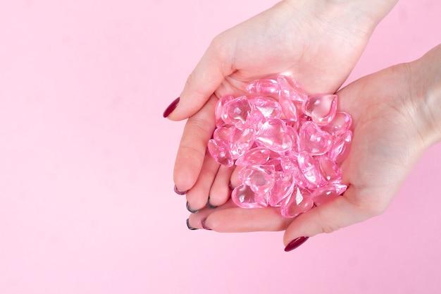 Viele glasherzen in den weiblichen händen auf einer rosa draufsicht.