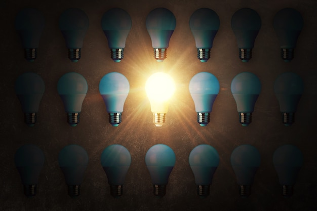 Viele glühbirnen und eine arbeitsglühbirne liegen auf einer konkreten textur, draufsicht. kreative idee und anders denken, konzept