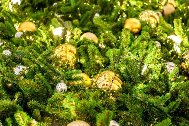 Viele goldene weihnachtskugeln schmückten die kiefer am weihnachtstag.