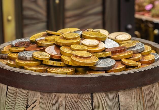 Viele goldmünzen auf einem hölzernen fass, das konzept des reichtums