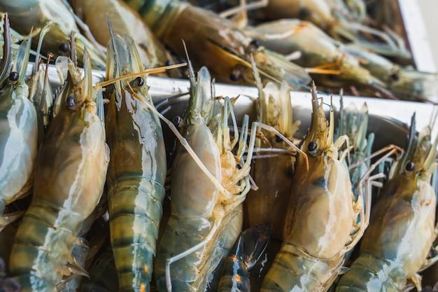 Viele große frische garnelen auf eis, in einem supermarkt. frische rohe meeresfrüchte im asiatischen traditionellen frischmarkt