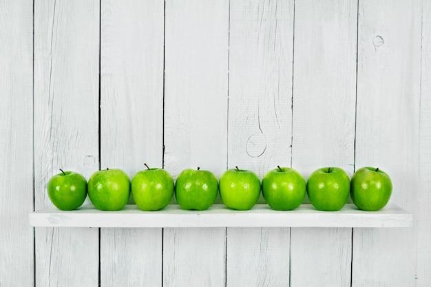 Viele grüne äpfel im regal. ein weißer hölzerner hintergrund.