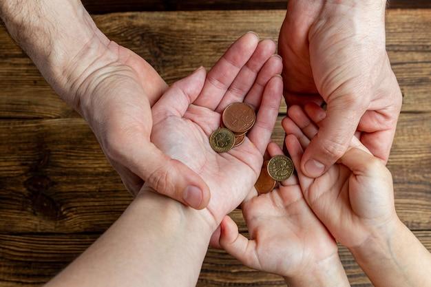 Viele hände halten münzen in den handflächen