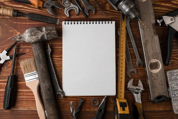Viele handlichen werkzeuge und leeres notizbuch auf holztisch, draufsicht