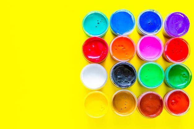 Viele helle farbdosen stehen zusammen auf einem gelben hintergrund mit einem platz für die textdraufsicht flach ...
