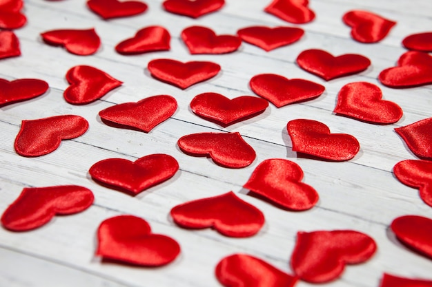 Viele herzen auf einem hölzernen hintergrund, das konzept der liebe und der treue