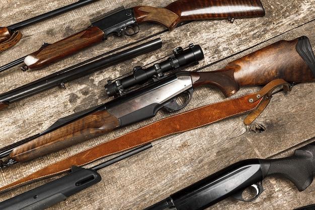 Viele jagdgewehre auf verwitterter holzoberfläche