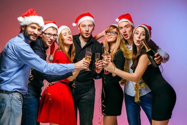 Viele junge frauen und männer, die an der weihnachtsfeier auf rosa studiohintergrund trinken