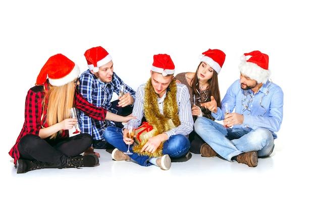 Viele junge frauen und männer, die an der weihnachtsfeier auf weißem studiohintergrund mit geschenk trinken