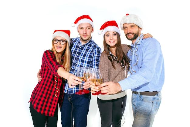 Viele junge frauen und männer, die an der weihnachtsfeier auf weißem studiohintergrund trinken
