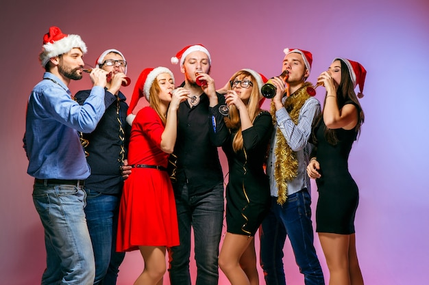 Viele junge frauen und männer trinken auf der weihnachtsfeier auf rosa studiohintergrund