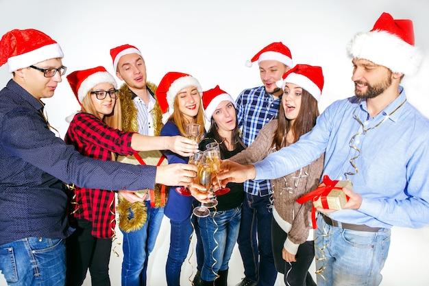 Viele junge frauen und männer trinken auf der weihnachtsfeier im weißen studio