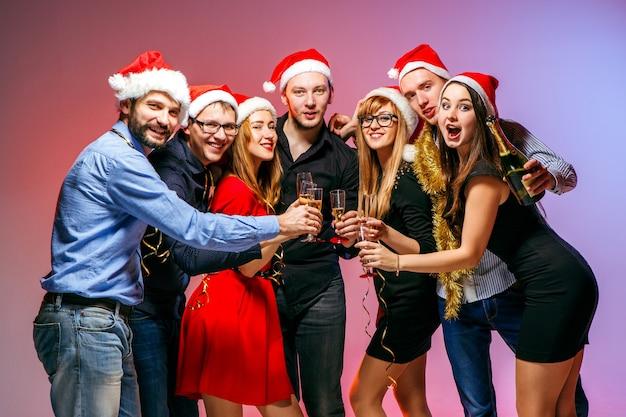 Viele junge frauen und männer trinken auf der weihnachtsfeier