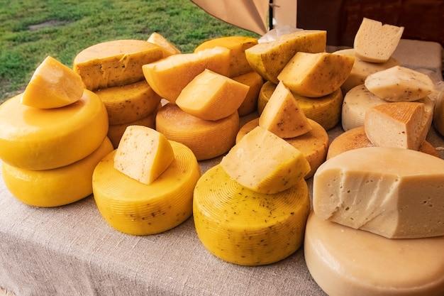 Viele käseköpfe verschiedener sorten aus natürlicher milch auf dem tisch mit leinentuch bedeckt
