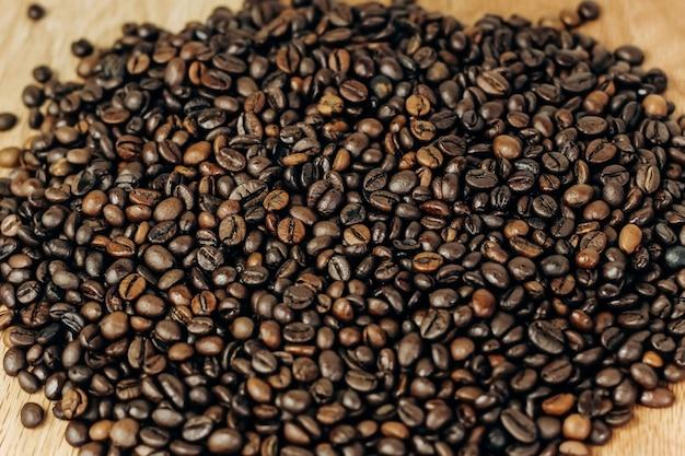 Viele kaffeebohnen auf einem hölzernen hintergrund. hintergrund und platz für text