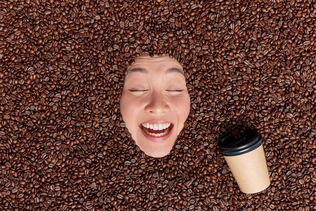 Viele kaffeebohnen um getränke espresso aus papier einwegbecher hält die augen geschlossen lächelt breit genießt angenehmes aroma oder duft