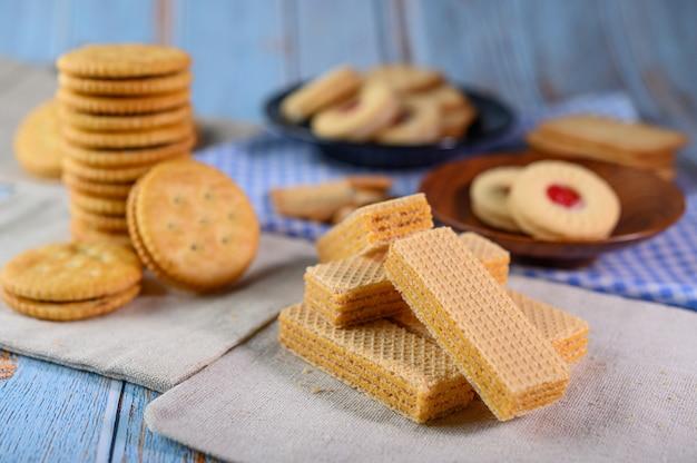 Viele kekse werden auf den stoff gelegt und dann auf einen holztisch gelegt.