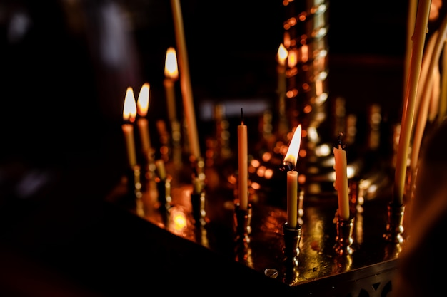 Viele kerzen brennen nachts in der kirche. gruppe brennender kerzen im dunkeln. nahansicht. speicherplatz kopieren.