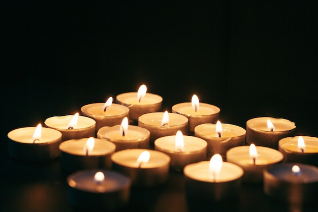 Viele kerzen brennen nachts. viele kerzenflammen leuchten auf dunklem hintergrund