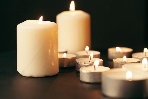 Viele kerzen brennen nachts. viele kerzenflammen leuchten im dunkeln