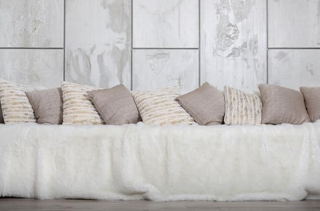 Viele kissen liegen auf der couch, die vor dem hintergrund einer marmorwand mit einem großen plüschschleier bedeckt ist