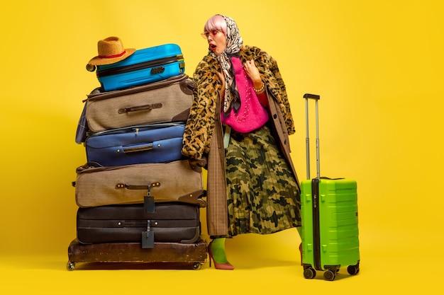 Viele klamotten für unterwegs. porträt der kaukasischen frau auf gelbem raum