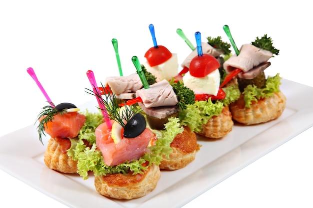 Viele kleine canape-sandwiches auf farbigen plastikspießen, auf einen teller gelegt, isoliert auf weißem grund.