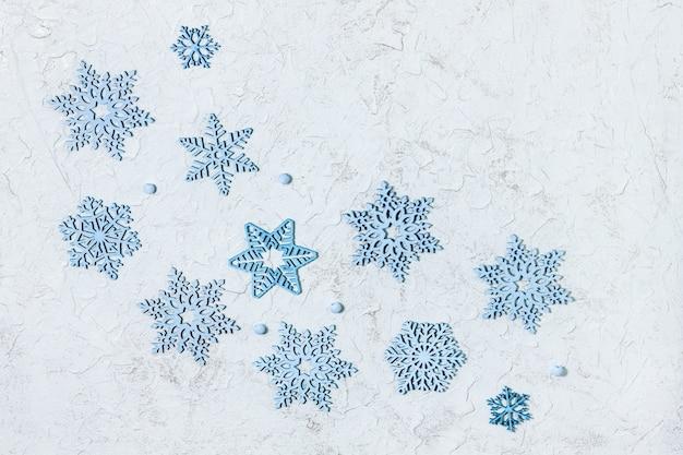 Viele kleine hölzerne dekorationen, blaue schneeflocken auf glänzendem hellem hintergrund.