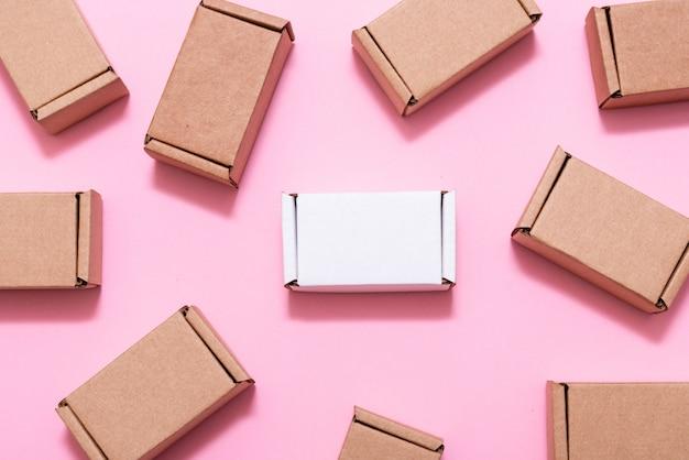 Viele kleine pappkartons auf rosa tisch