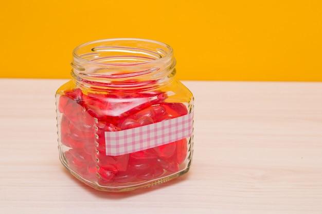 Viele kleine rote glasherzen in einem glas mit einem aufkleber zur beschriftung, einem glas mit herzen auf dem tisch, gelber oberfläche, wohltätigkeit und selbstlosem hilfekonzept, valentinstag