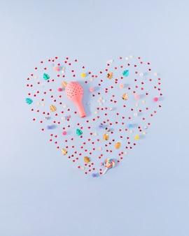 Viele kleine rote herzen konfettiballon und andere party-requisiten machen die form des herzens
