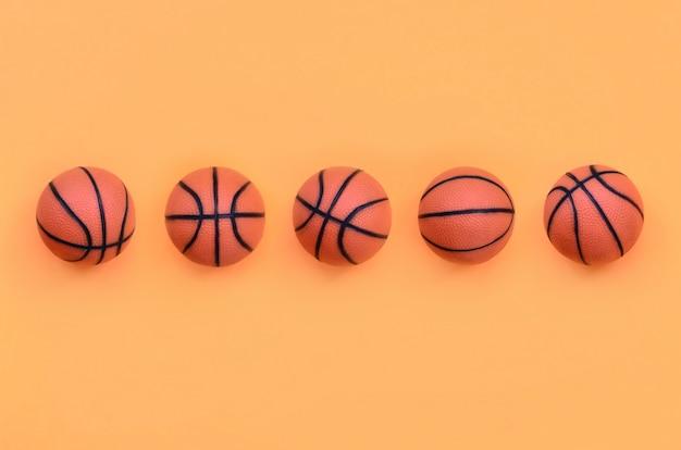 Viele kleinen orange bälle für basketballsportspiel liegen auf beschaffenheitshintergrund