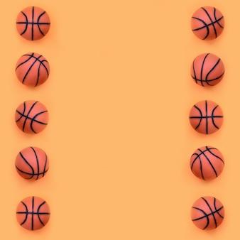 Viele kleinen orangefarbenen bälle für basketball-sportspiel liegen auf orangefarbenem modepastellpapier